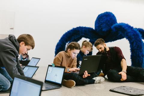 Kinder arbeiten mit einem Kunstvermittler am Laptop im Programm ScratchLab