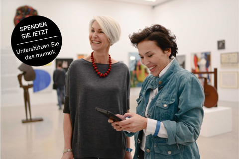 """Zwei Damen mittleren Alters in einer Ausstellung stehend und lachend mit eine mStörer mit der Aufschrift: """"Spenden Sie jetzt- unterstützen Sie das mumok"""""""