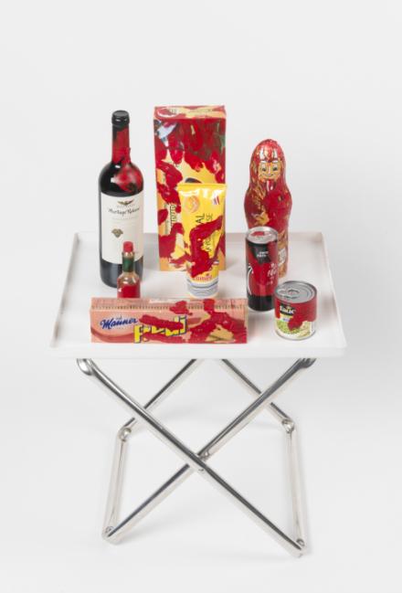 ein Klapptisch auf dem eine Weinflasche, Kekse, ein Schokokrampus, tapasco und Dosen stehen. Alles mit Roter Farbe bekleckert als ob eine bluntende Hand es Angefasst hätte
