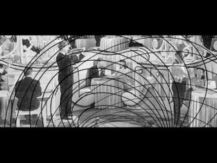 Ein Schwarzweiß Bild - Ein Mann der Geige Spielt und ein Mann der am Klavier sitzt in einem Kaffee, die Aufnahme scheint alt zu sein. Eventuell die 1930er? Wieder mit den schwarzen Strichen im Vordergrund
