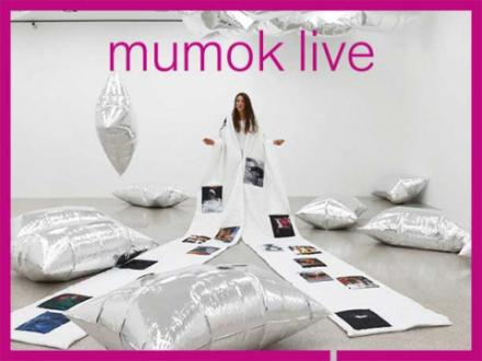 Frau mit weißer Robe und darauf abgebildeten Bildern steht in Raum umringt von Silvercoulds von Andy Warhol