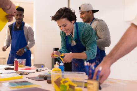 Das Bild zeigt eine Kunstvermittlerin beim Basteln mit Personen mit und ohne Migrationshintergrund.