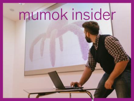 Benedikt Hochwartner vor einem Screen und Laptop