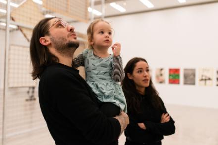 Eine Familie betrachtet ein Kunstwerk. Der vater trägt ein kleines Kind wärend die Mutter daneben steht und sie gemeinsam ein Bild betrachten welches sich auserhalb es Fotos befindet