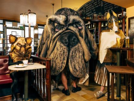 Die Fotografie von Hugo Canoilas zeigt Personen in Hundekostümen in einem Wiener Cafe. Besondern auffällig ist der große Hundekopf im zentrum des Bildes.
