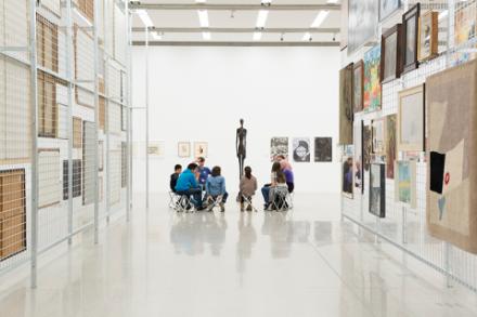 Besucher sitzen bei einer Fürhung durch das Museum