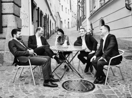 Mehrere menschen sitzen um einen runden Tisch auf einer gepflasterten Straße und Lachen