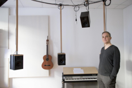 Im Hintergrund steht ewin Keyboard und eine Gitarre hängt an der Wand. Von der Decke hängen zwei Boxen. Rechts steht der Musiker Volkmar Klien