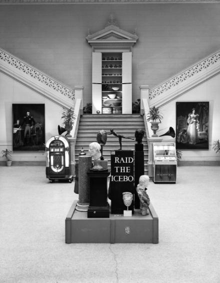 """Installationsansicht von der Ausstellung """"Raid the Icebox"""" Schwarz-weiß Fotografie einer Halle mit Stiegen nach oben und vor den Stiegen ein Podest mit verschiedenen Büsten"""