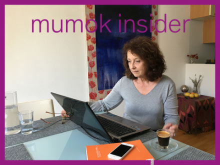 Frau sitzt vor ihrem Notebook im Wohnzimmer