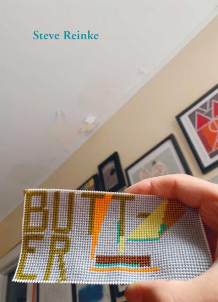 Coverbild der Publikation Steve Reinke. Butter. Zusehen ist eine hand die eine Stickerei hochhält auf der Butt- und in der nächsten zeile ER steht. Das Foto scheint in einem Wochnzimmer aufgenommen zu sein