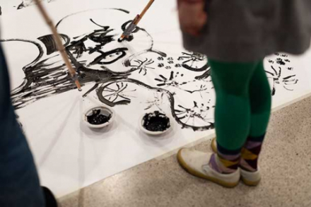 Papier auf dem Boden auf welches mit schwarzer Farbe gemalt wird