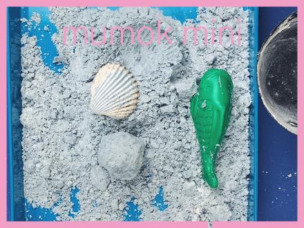 Sand mit Muschel und einem Plastikfisch