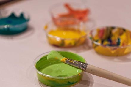 Das Bild zeigt mehrere Schalen mit Farben sowie einen Pinsel mit grüner Farbe.